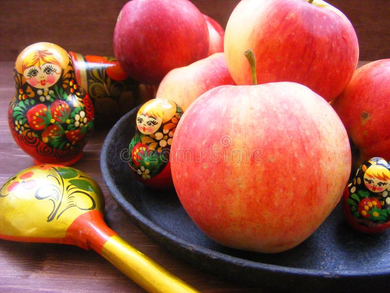 Russian cuisine. Composition of red and yellow apples on black cast iron plate with traditional russian nesting dolls matrioshka royalty free stock photo