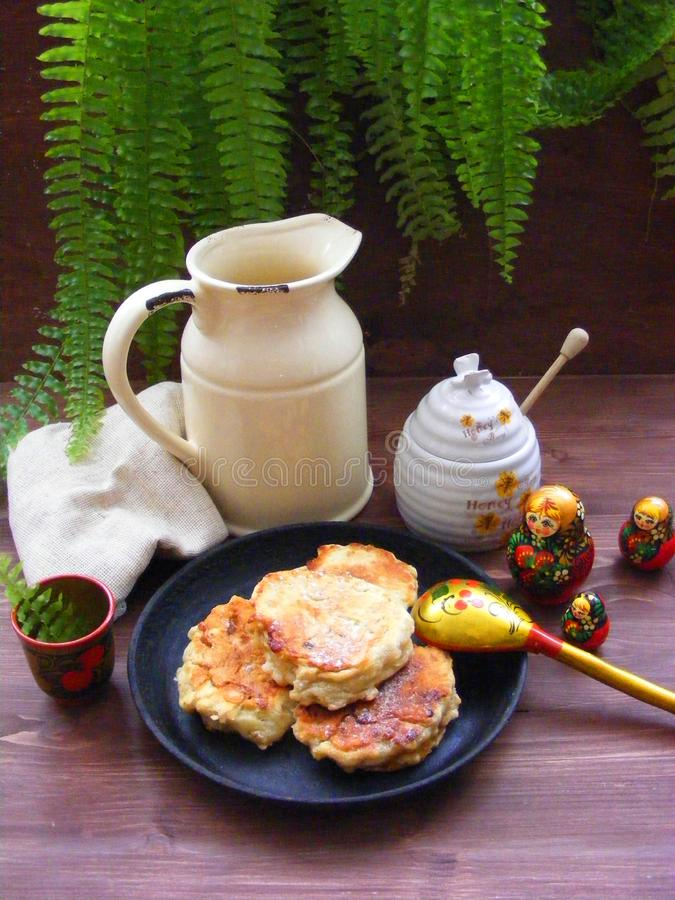 Russian cuisine : crepes pancakes on black cast iron with oak flakes on wooden background with rustic milk jug and nesting dolls. Russian cuisine - crepes stock images