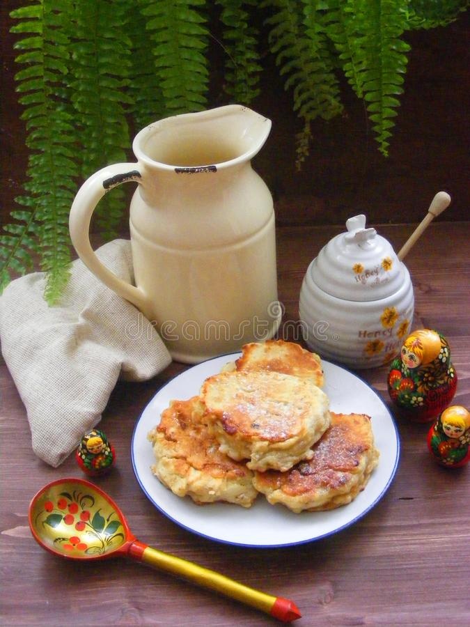 Russian cuisine : crepes pancakes with oak flakes on brown wooden background with rustic milk jug and nesting dolls matrioshka ve. Russian cuisine, crepes royalty free stock images
