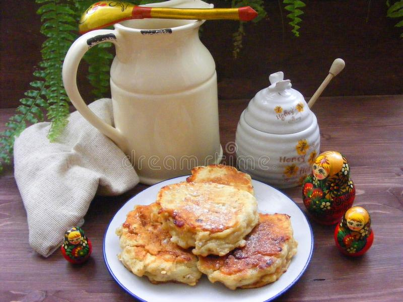 Russian cuisine : crepes pancakes with oak flakes on  shabby wooden background with rustic milk jug and nesting dolls matrioshka. Russian cuisine : crepes royalty free stock photo