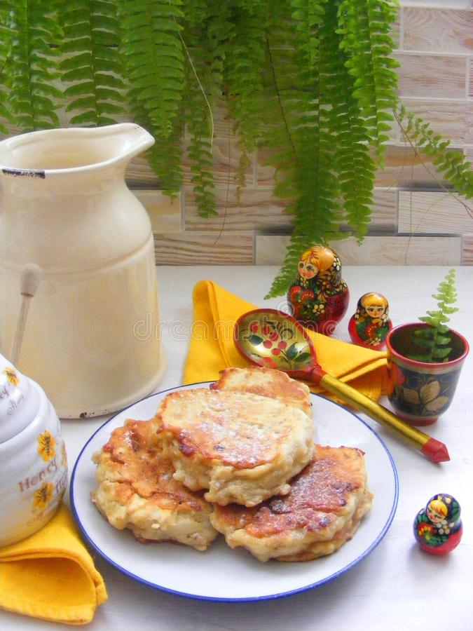 Russian cuisine : crepes pancakes with oak flakes on shabby wooden white background with rustic milk jug and nesting dolls. Matrioshka stock photo