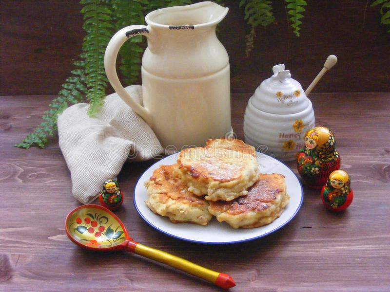 Russian cuisine : crepes pancakes with oak flakes on wooden background with rustic milk jug and nesting dolls matrioshka. Russian cuisine, crepes pancakes with royalty free stock photo