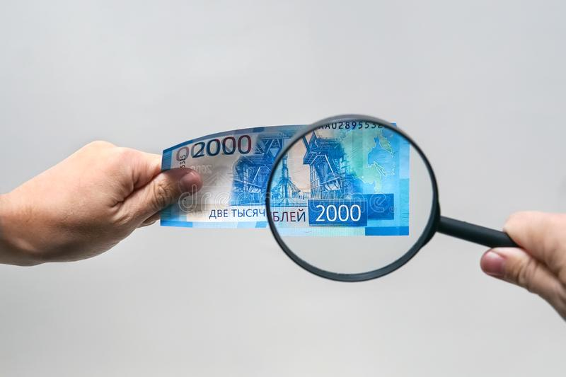 Russian currency, including new 2000 rouble bills. men's hands hold 2000 rubles and a magnifying glass. verification of the authe royalty free stock photo