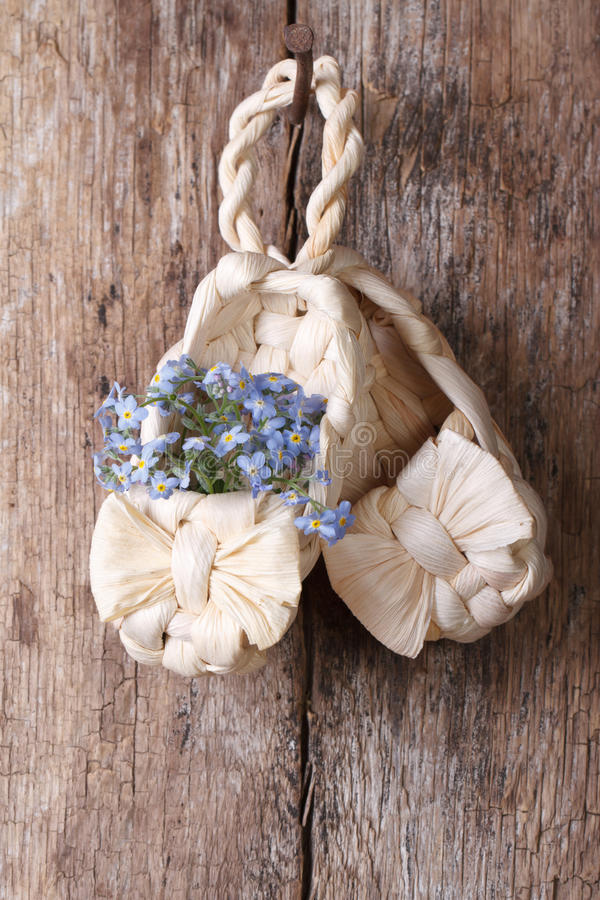 Russian decor: baby bast shoes with flowers forget-me-not royalty free stock photo