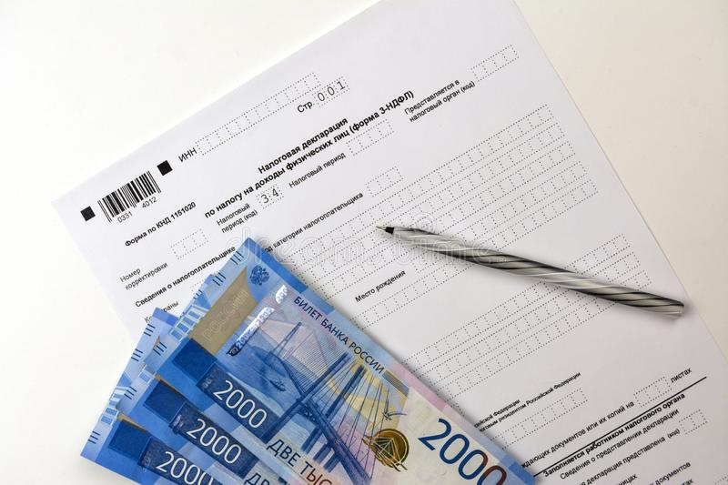 Russian documents, income Declaration Form 3-NDFL, cash 2000 rubles and a pen. On white royalty free stock image