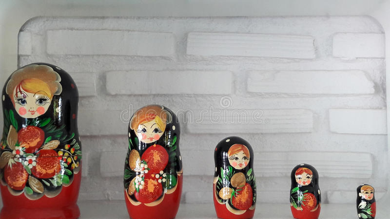"""Russian dolls with white brick wall. Russian dolls or Nesting dolls are called as """"Matryoshka"""" in Russian language. It is not only popular souvenir from royalty free stock photos"""