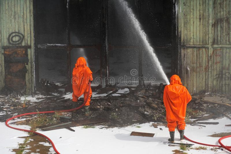 Russian Emergency Control fire drill in orange protective suits. Extinguishing fire horizontal stock images