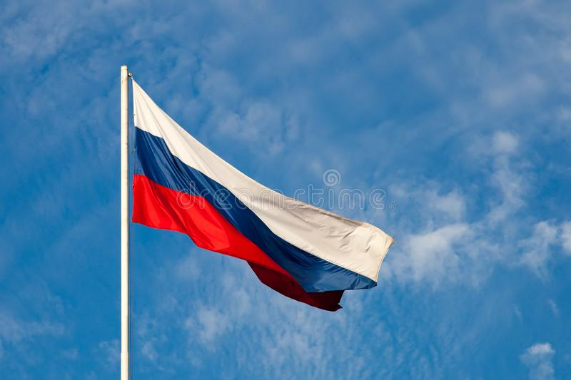 Russian flag  close-up on a pole against a blue sky. The Russian flag develops in a wave in the wind royalty free stock photos