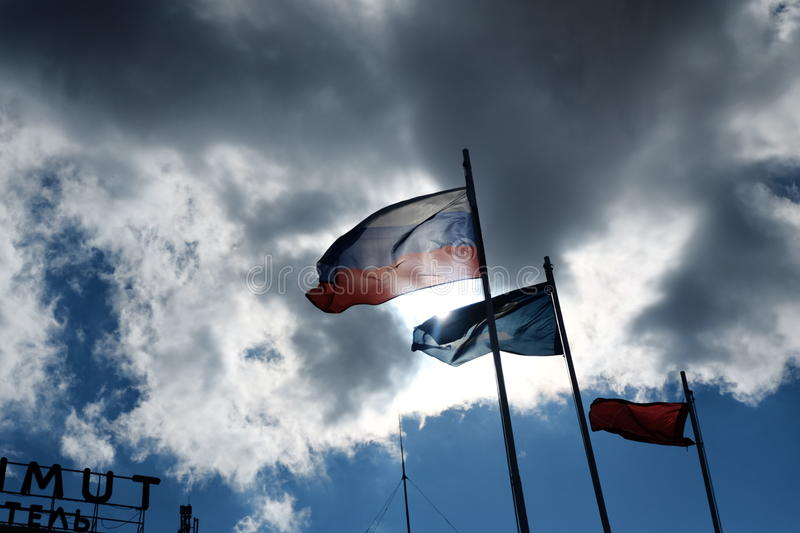 Russian flag on the wind against damatic clouds. And flag of the Astrakhan region next stock photography