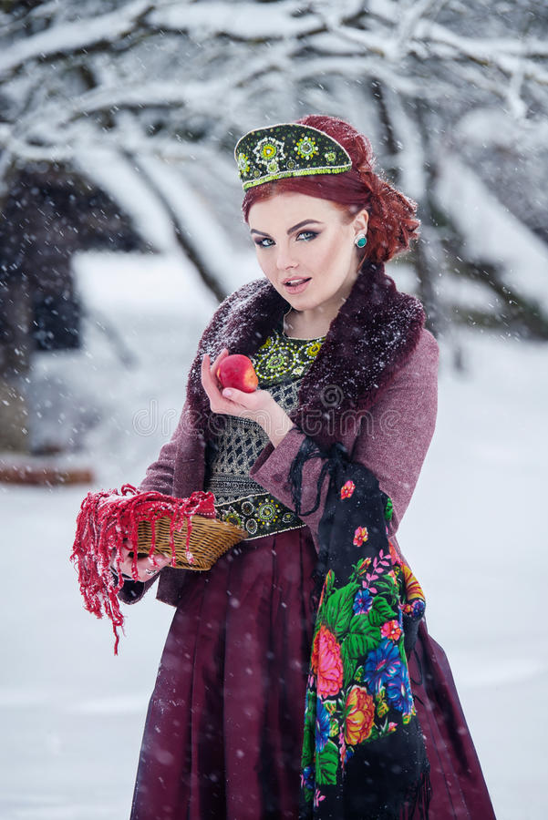 Russian folk style redhead girl holding an apple in a fur coat in winter. Russian folk style redhead girl holding an apple in a fur coat in winter stock images