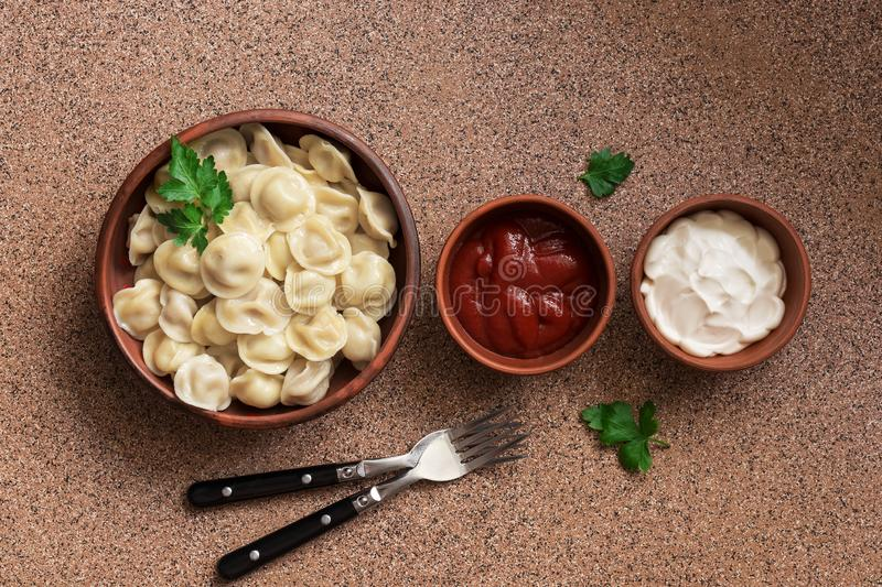 Russian food pelmeni meat dumplings with sour cream and ketchup arranged in a row on brown stone background . Overhead view, copy royalty free stock photo
