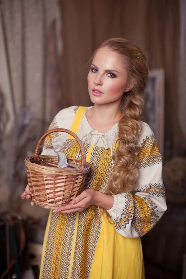 Russian girl with long braid. A beautiful Russian blonde girl in a yellow sundress with a long braid holds a basket in her hands royalty free stock photography