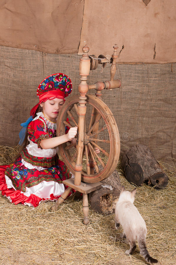 Russian girl in national dress. Russian girl in national costume, playing with the cat stock photo