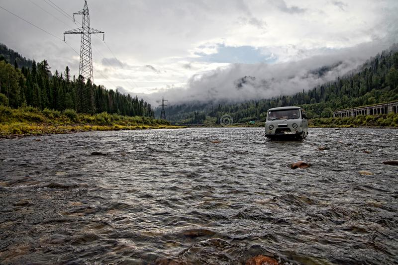 Russian gray SUV crosses the mountain river with power lines on the left bank and a railway line on the right bank with low clouds royalty free stock photography