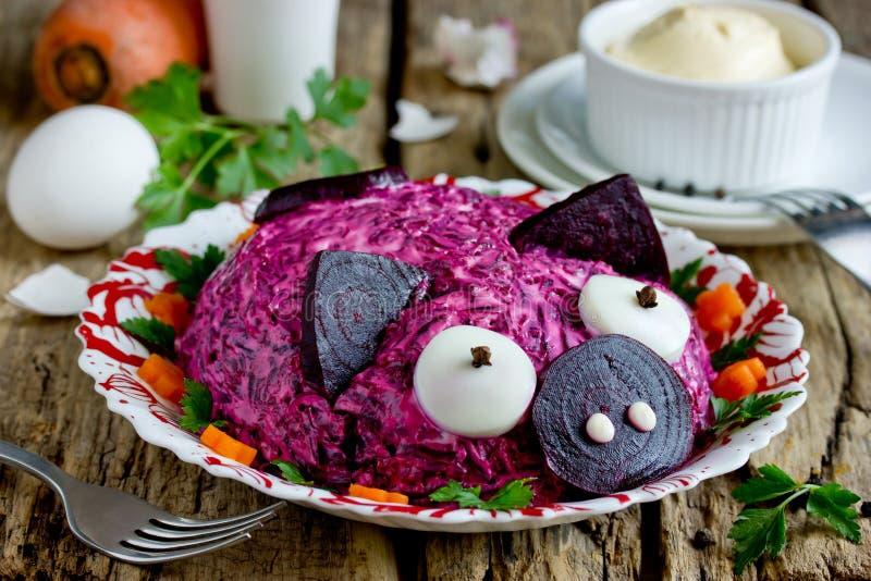 Russian herring under fur coat salad or dressed herring shaped funny pink pig stock photo