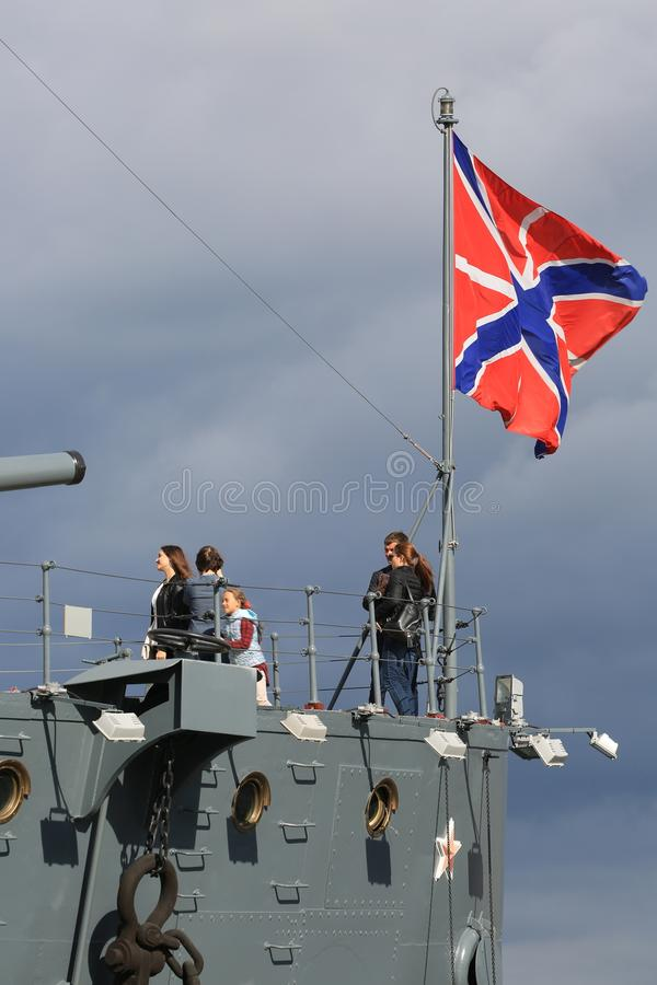 People near naval jack of Russia against the background of a cloudy sky stock images