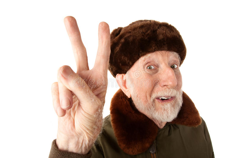 Russian Man in Fur Cap Making Peace Sign. Senior Russian Man in Fur Cap and Jacket Making Peace Sign stock image