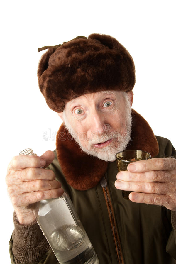 Russian Man in Fur Cap with Vodka. Senior Russian Man in Fur Cap and Jacket with Vodka stock images