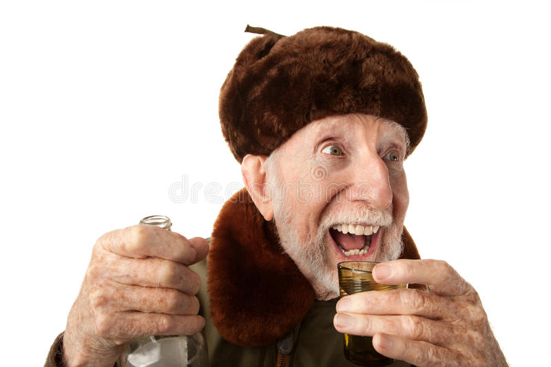 Russian Man in Fur Cap with Vodka. Senior Russian Man in Fur Cap and Jacket with Vodka stock photo