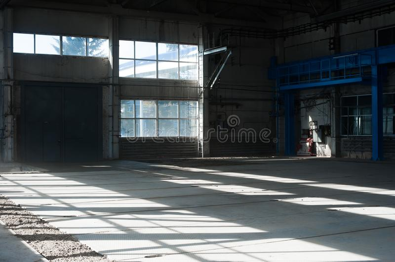Manufacturing factory. Empty hangar building. Blue toned background. The production room with large windows and metal structures. Russian manufacturing factory royalty free stock images