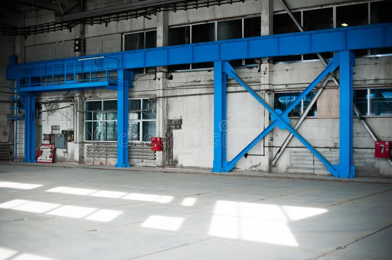 Manufacturing factory. Empty hangar building. Blue toned background. The production room with large windows and metal structures. Russian manufacturing factory royalty free stock photo