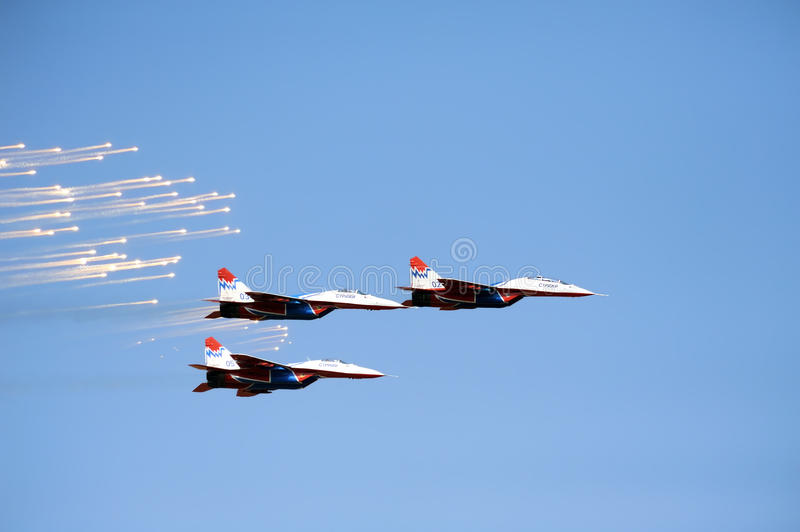 Russian Mig 29 M2 fighter plane releasing infrared countermeasure decoys. BATAJNICA, SERBIA - SEPTEMBER 2: Russian Aerobatic Team Strizi with 3 Mig 29 M2 fighter stock photography