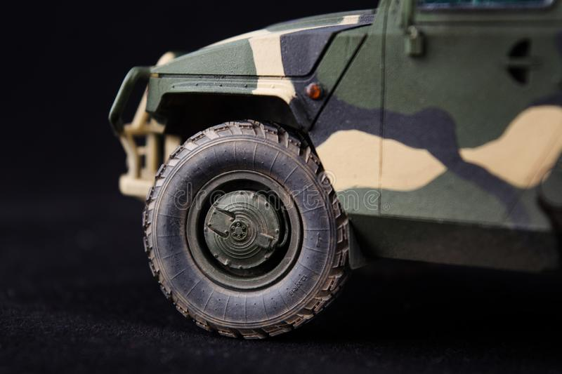 Russian military armored camouflage jeep Tiger. Closeup view. Plastic scale model on dark background royalty free stock photo