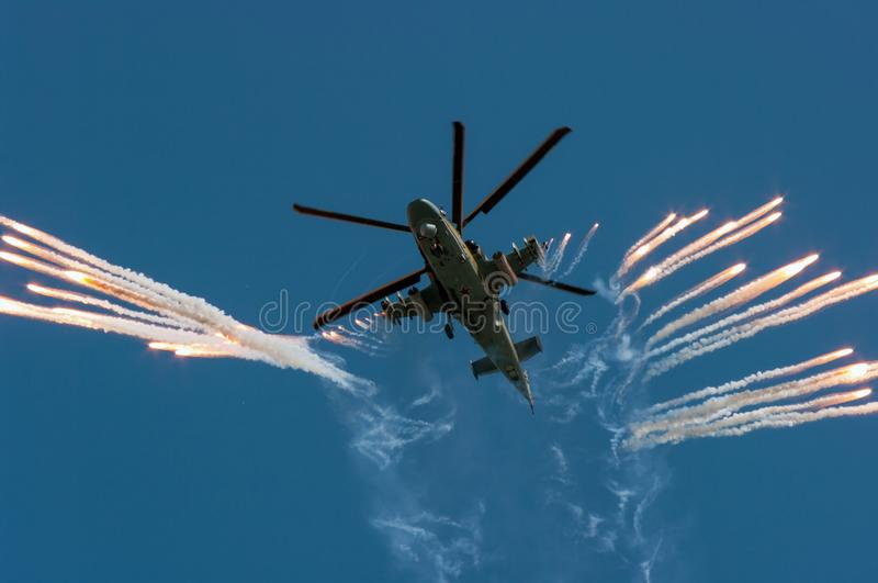 Russian military helicopter Ka-52 fires off heat decoy on air-show royalty free stock images