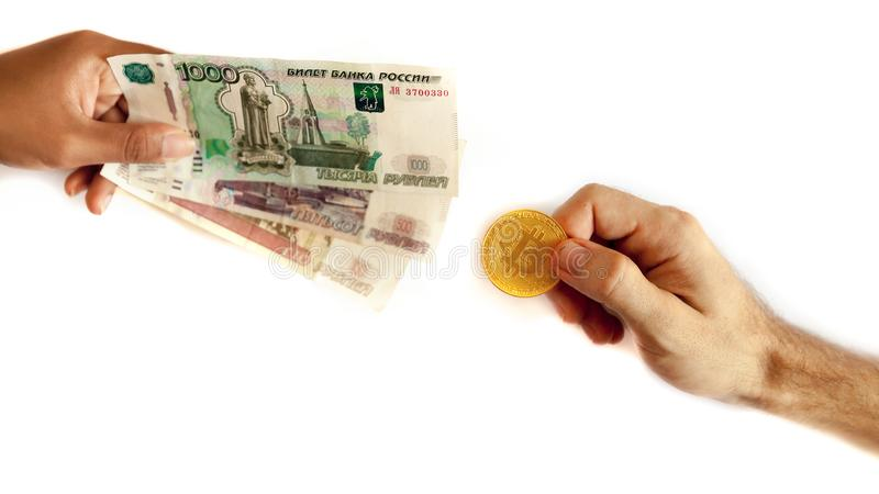 Russian money and bitcoin in the hand of people. Exchange, sale and purchase the Russian ruble and the new world international crypto currency btc bit coin on royalty free stock images