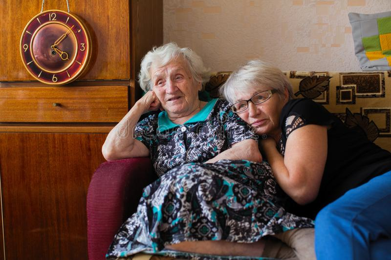 Russian old woman with her adult daughter sitting together at home watching on TV Putin`s speech. Travel. royalty free stock photo