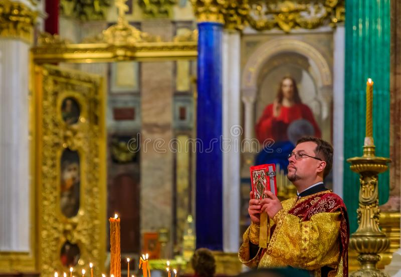 Russian Orthodox priest in traditional clothing serving in the Saint Isaac`s Russian Orthodox Cathedral in Saint Petersburg Russi stock photos