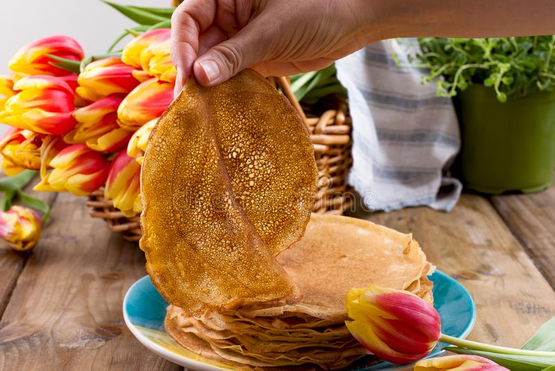 Russian pancakes with butter on a wooden background. A bouquet of fresh spring tulips and traditional Russian food. Free space for. Text stock photo