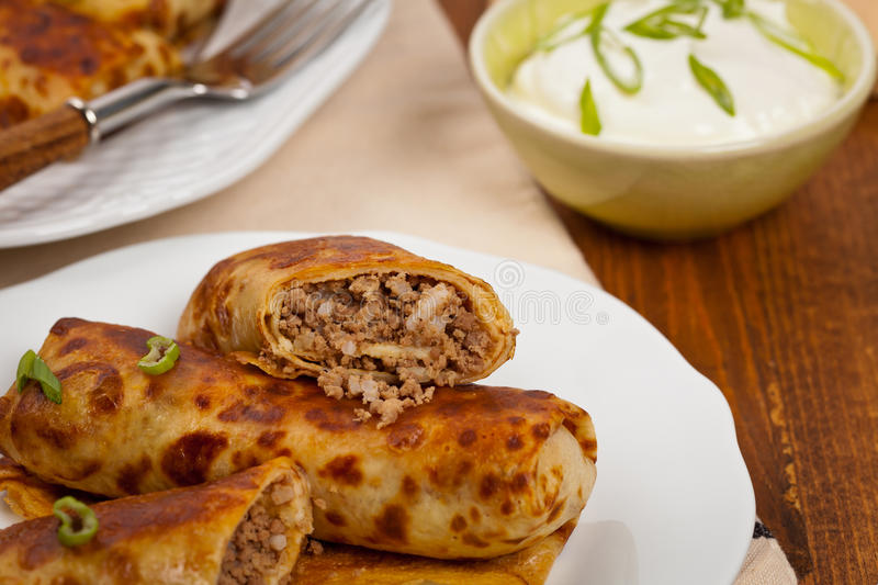 Russian Pancakes with Meat. Traditional Russian Fried Stuffed Pancakes Blintzes with Meat. Selective focus royalty free stock photo