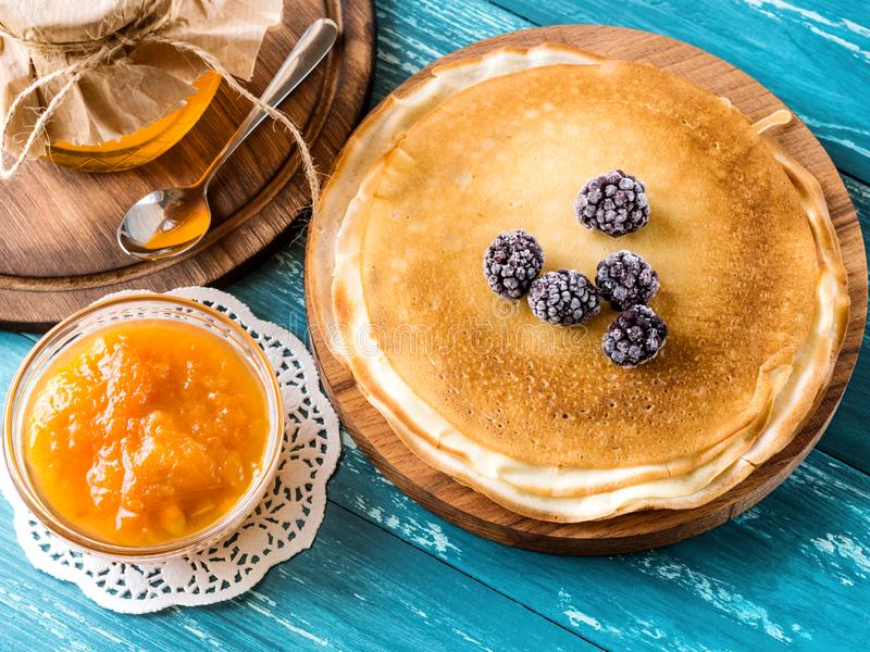 Russian pancakes on a wooden plate on an azure table with frozen blackberries, apricot jam and honey on an azure background. The russian pancakes on a wooden stock photography