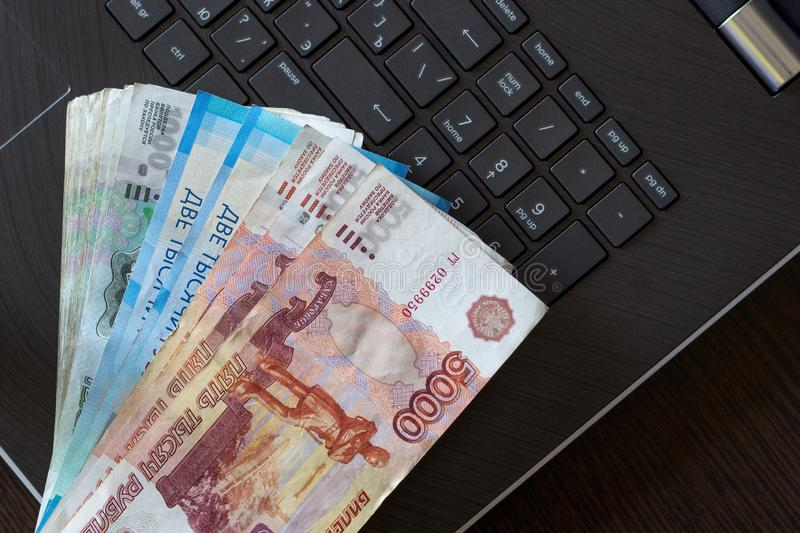 Russian paper currency on laptop keyboard. Bundle rubles from different large nominal banknotes folded like a fan. Freelance earnings concept. Cash payments stock photos
