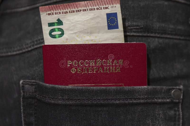 Russian passport and a bill of 10 euros stick out of the back pocket of jeans royalty free stock images