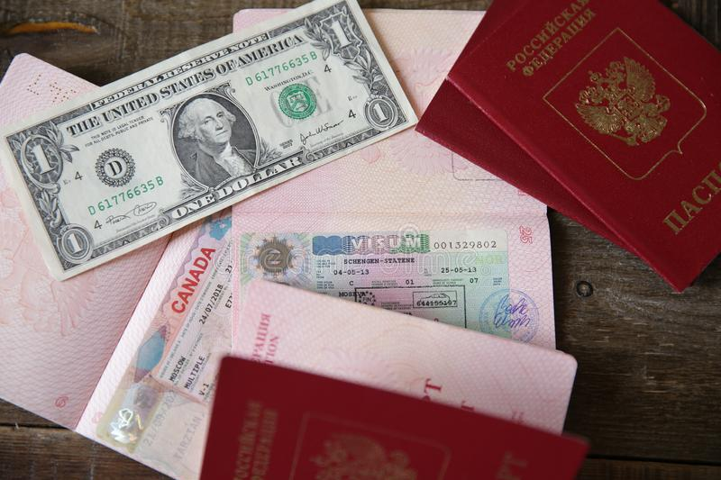 Russian passport with a Canadian and Schengen visa and money - one dollar. Visa stamp travel passport. Vacation and travel. Concept stock photography