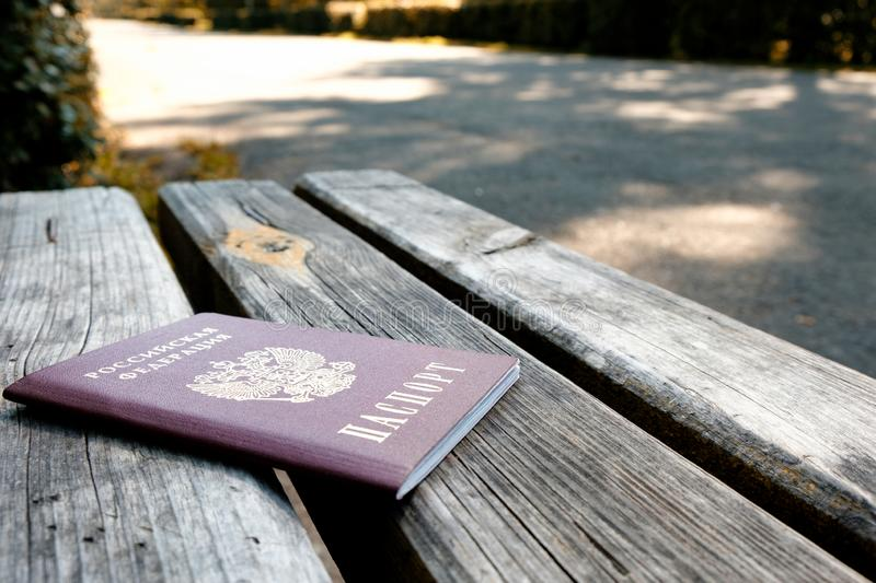 Russian passport on a wooden bench on a summer day, the background of the paved path royalty free stock photography