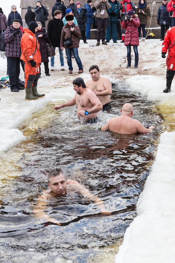 Russian people are dipped into an ice hole on the day of the Epiphany, St. Petersburg. SAINT-PETERSBURG, RUSSIA - JANUARY 19, 2016: Russian people are dipped stock photo