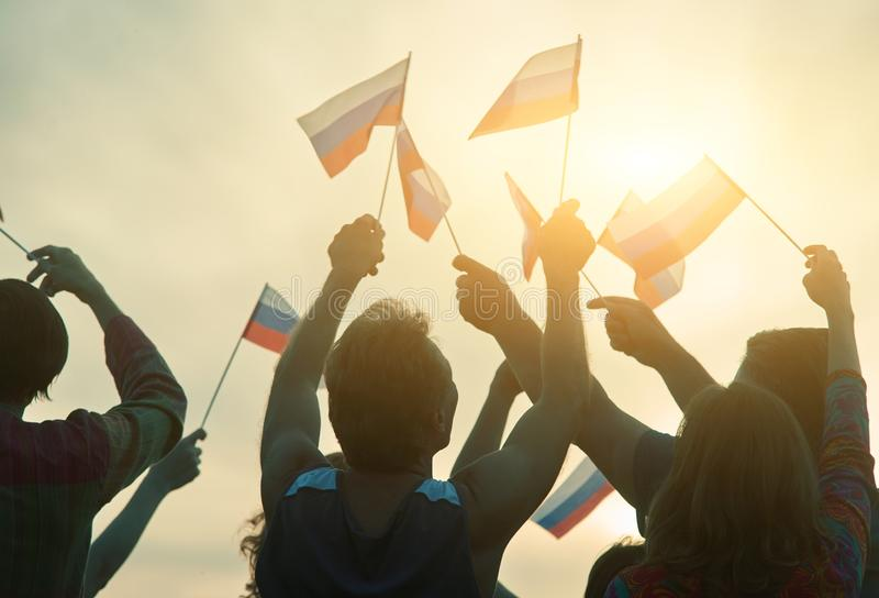 Russian people with small flags, back view. Glowing morning sun background stock image