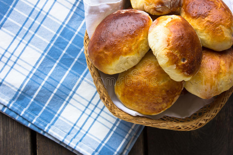Russian pirozhki, baked patties or pies on basket with jug of milk. top view royalty free stock photo
