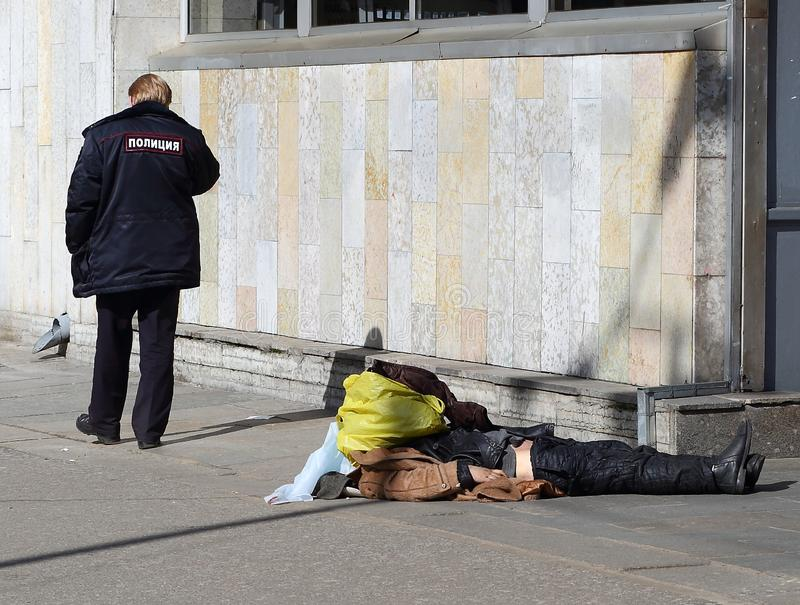 Russian police calls the outfit to the body of a dead homeless man at the wall of the metro station. Ulitsa Kollontai, St. Petersburg, Russia stock photography