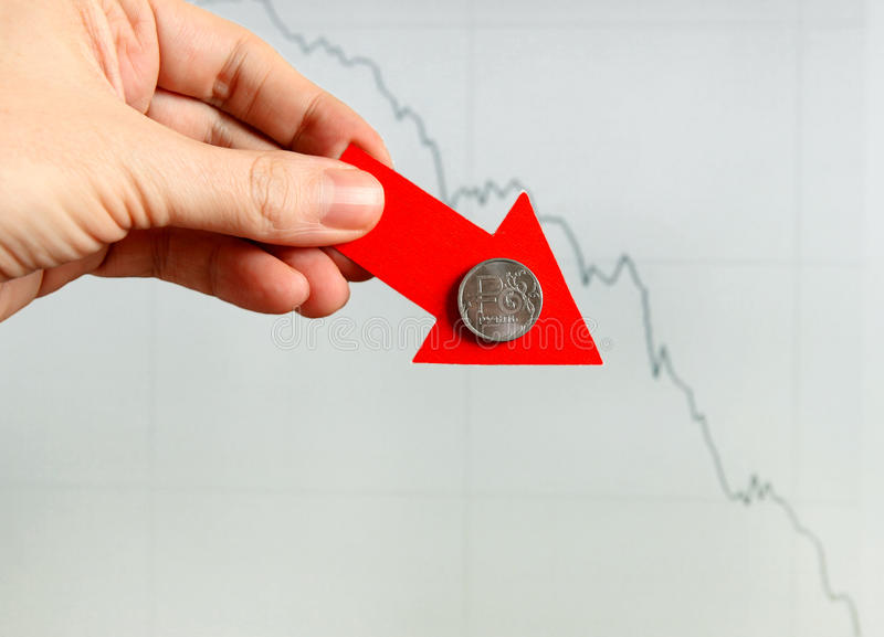 Russian Ruble Down. Red Arrow in a Hand with Russian Ruble Down on the Diagram Background stock photography