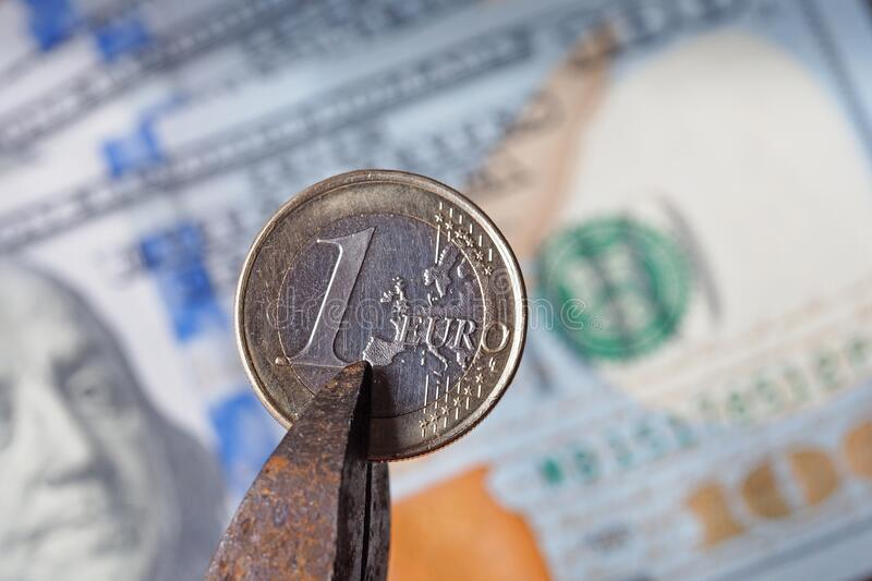 Russian ruble sandwiched in nippers against the background of US dollars royalty free stock photography