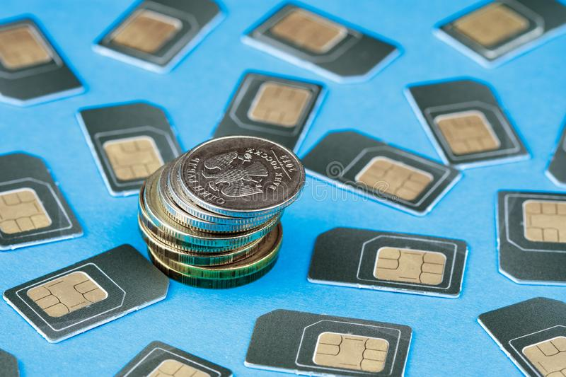 Russian rubles coins stacked in piles near the scattered gray SIM cards for your phone. Blue background stock photos