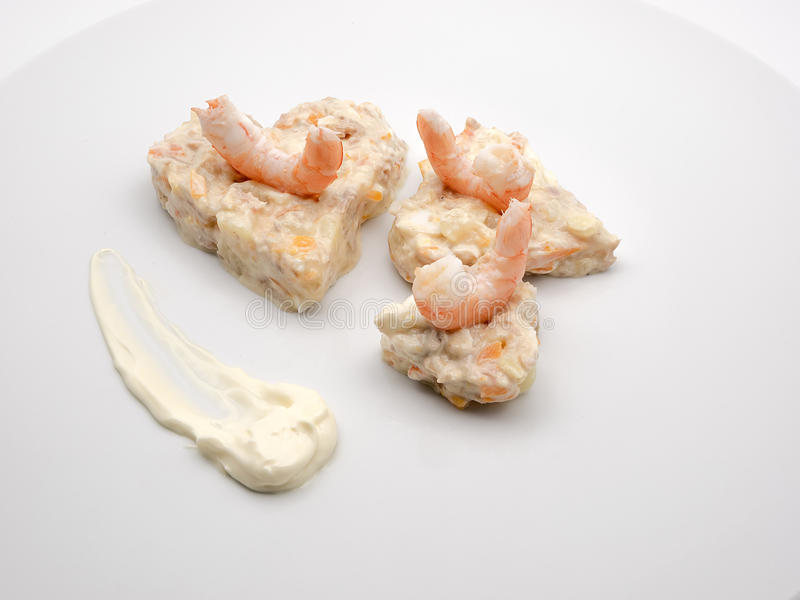 Russian salad with king prawns on white plate royalty free stock photo
