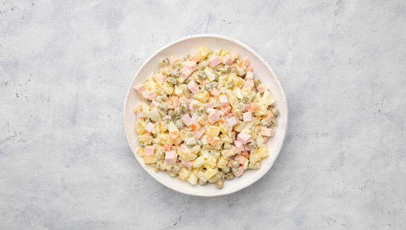 Russian salad Olivier with mayonnaise on plate. Light background. Top view, flat lay stock images