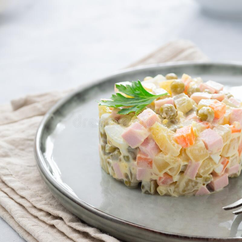 Russian salad Olivier with mayonnaise on plate. Russian salad Olivier with mayonnaise served in culinary ring on plate. Light background stock image