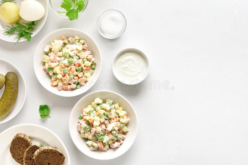 Russian salad \'Olivier. Traditional russian salad \'Olivier\' from boiled vegetables and sausage with mayonnaise in bowl. Russian New Year or Christmas salad on royalty free stock image