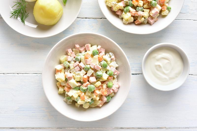 Russian salad \'Olivier. Traditional russian salad \'Olivier\' from boiled vegetables and sausage with mayonnaise in bowl. Russian New Year or Christmas salad on stock photos